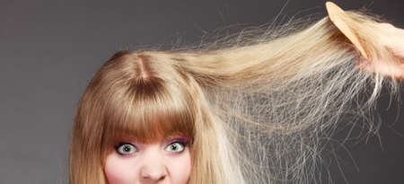 eyed: Haircare. Blonde woman with her damaged dry hair wide eyed gray background Stock Photo