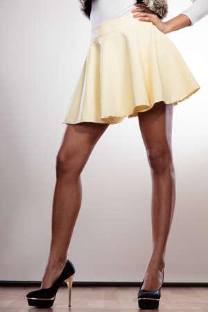 piernas con tacones: Atractivas delgadas piernas de raza mixta africano chica mujer caucásica en la falda en tacones altos.
