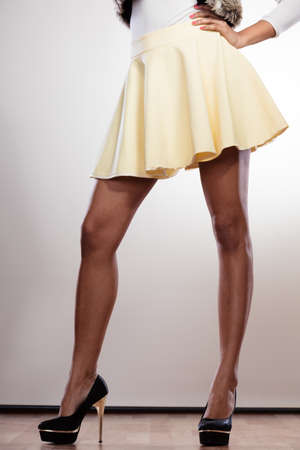Attractive slim legs of mixed race african caucasian woman girl in skirt on high heels. Stock Photo