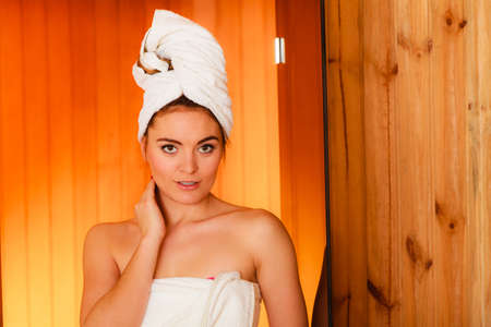 sauna: Spa beauty treatment and relaxation concept. Woman white towel relaxing in wooden sauna room.