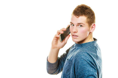 mobile communication: Technology and communication. Young man casual style talking on mobile cell phone using smartphone isolated on white