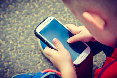 Little boy child kid playing games on smartphone mobile phone outdoor. Technology generation. Foto de archivo