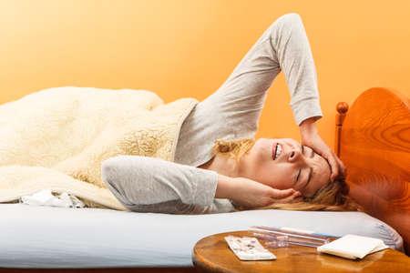 Chora kobieta cierpi na ból głowy ból. Chora dziewczyna r w łóżku przeziębił. Termometr i tabletki na stole.