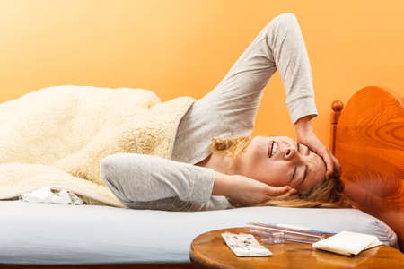 Sick woman suffering from headache pain. Ill girl laying in bed caught cold. Thermometer and pills on table. Stockfoto