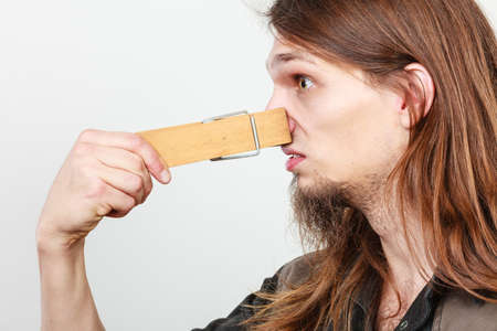 unpleasant: Unpleasant bad smell concept. Portrait of young long haired man with clogged nose by big clothespin.