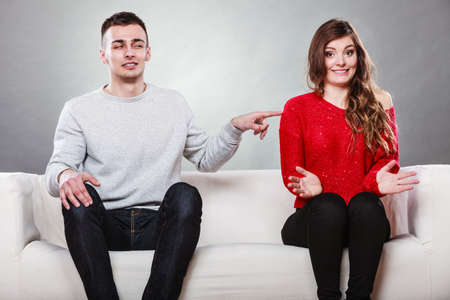next to each other: Shy woman and man sitting on sofa couch next each other. First date. Attractive girl and handsome guy meeting dating and trying to talk. Male touching picking up female.
