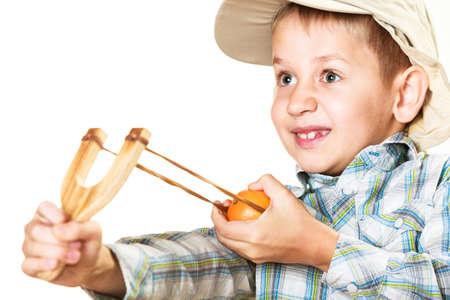 niños malos: Niños de crianza problemas. Kid sosteniendo tirachinas en las manos. Niño travieso malo dispara desde un cabestrillo de madera en blanco Foto de archivo