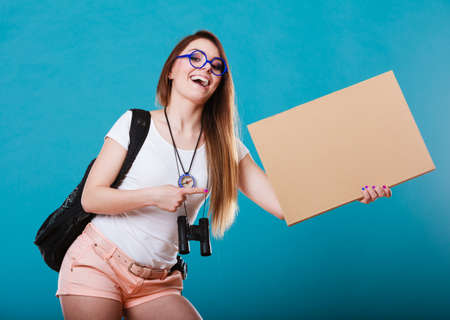 billboard: Travel and tourism active lifestyle concept. Woman tourist hitchhiking with blank sign for text on blue