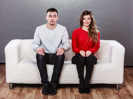 Shy woman and man sitting on sofa couch next each other. First date. Pretty girl and handsome guy meeting dating and trying to talk.