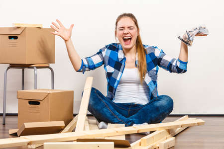 Worried woman moving into new apartment house assembling. Young girl holding screws and furniture parts arranging interior and unpacking boxes.