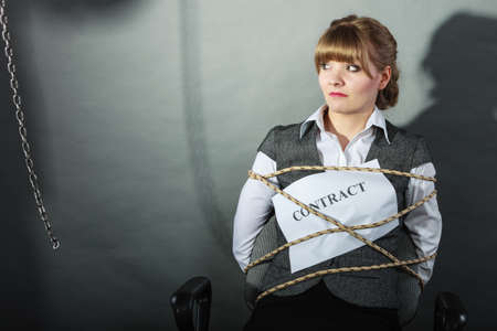 Upset businesswoman bound by contract terms and conditions.  Helpless woman tied to chair become slave. Human shadow in background. Business and law concept.