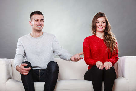 couple dating: Shy woman and man sitting on sofa couch next each other. First date. Attractive girl and handsome guy meeting dating and trying to talk. Male offering a hand to female. Stock Photo