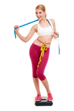 measures: Slimming and weight loss. Happy joyful young woman girl measuring with tape measures on weighing scale. Healthy lifestyle concept. Isolated on white. Stock Photo
