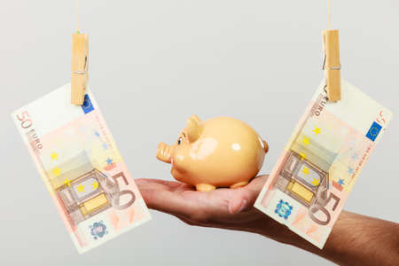 spending money: Spending money concept. Male hand with piggybank and euro banknote cash hang on laundry line. Savings.