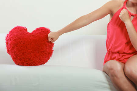 Human hand punching hitting red heart shape pillow. Valentines day love.