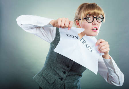 unsatisfied: Business, documents and legal concept - serious unhappy businesswoman tearing crumpled contract Stock Photo