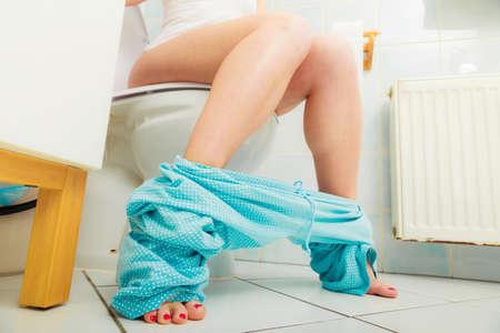 papel de baño: Mujer con el estreñimiento o la diarrea se sienta en tocador con su pijama azul alrededor de sus piernas