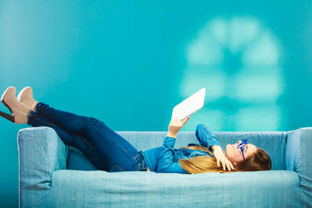 Modern technology education internet concept. Fashion student girl in glasses with tablet relaxing on blue color Banque d'images