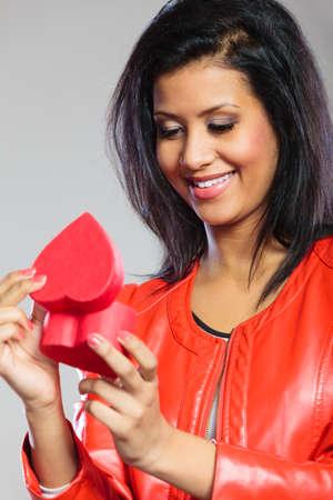 Concepto de día de San Valentín. Encantadora linda chica africana en elegante chaqueta roja con presente de regalo de caja de corazón. Tiempo de amor.