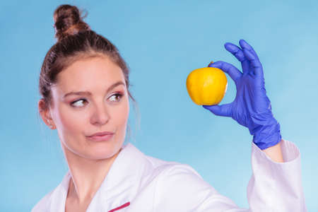 Scientist doctor with rotten apple. Woman chemist holding genetically modified fruit. GM food modification. Stok Fotoğraf