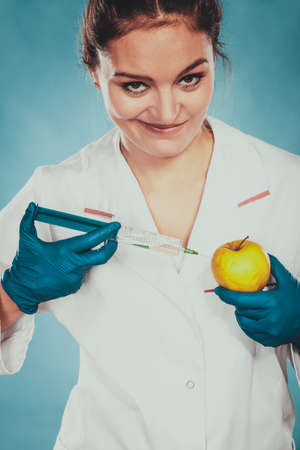 Scientist doctor injecting apple with syringe. Woman chemist holding genetically modified fruit. GM food modification.