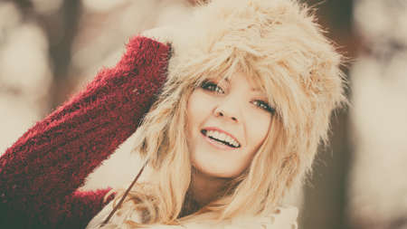 Portrait of pretty smiling fashionable woman in fall forest park. Happy gorgeous young girl in fur winter hat and sweater pullover. Autumn fashion. Instagram filter.