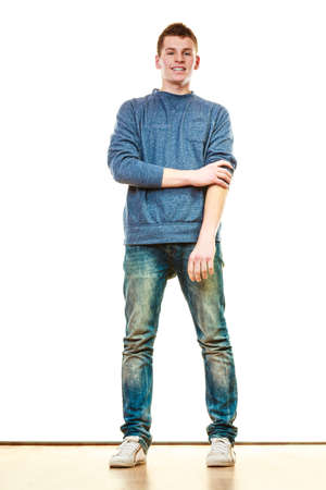Young fashionable man teen boy in full length casual style blue jeans posing isolated on white