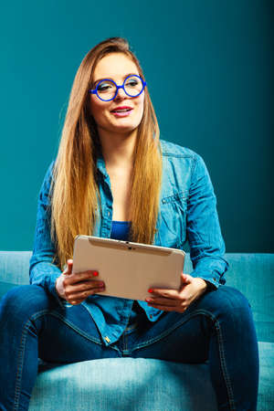 e book device: Modern technologies leisure and young people concept. fashionable woman wearing jeans with tablet sitting on couch blue color