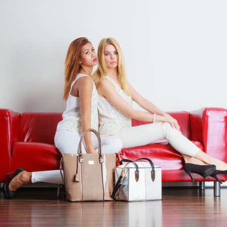 handbag model: Elegant outfit. Female fashion. Two women blonde and mixed race wearing fashionable clothes high heels with bags handbags sitting on red couch.