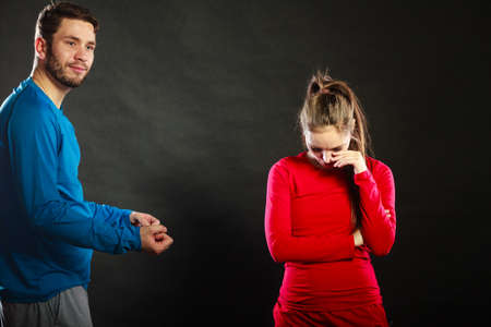 insulted: Man husband talking to offended insulted woman wife in studio on black.