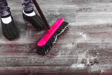 brooming: Cleanup housework concept. Closeup broom and female foots. Cleaning woman sweeping wooden floor. Stock Photo