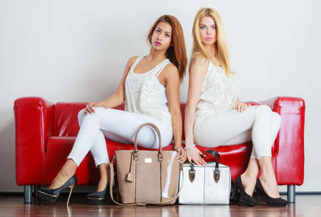 couch: Elegant outfit. Female fashion. Two women blonde and mixed race wearing fashionable clothes high heels with bags handbags sitting on red couch.