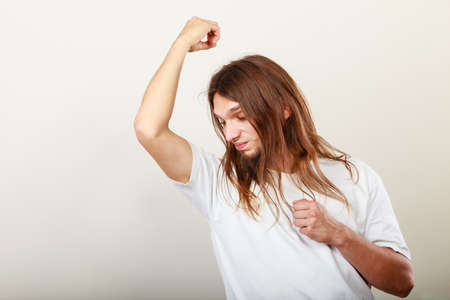 bad breath: Expression of very bad smell. Young long haired sweaty man making hand gesture. Sweating concept.