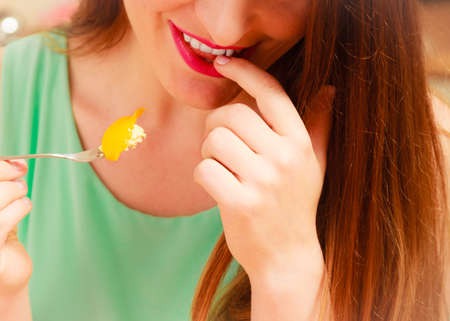 gluttony: Woman eating delicious gourmet sweet cream cake cupcake with fruits. Glutton girl having breakfast in kitchen. Appetite and gluttony concept.