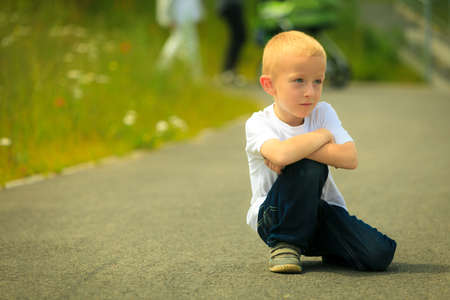Portrait of thoughtful, pensive little boy child or kid in summer park.