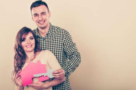 Sourire jeune couple tenant maison de papier et la clé. Mari et femme rêvant de nouvelle maison. Logement et concept immobilier.