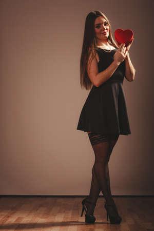 sexualidad: La belleza, la sexualidad y la seducci�n. Joven atractivo modelo atractivo de la mujer de longitud completa con el coraz�n rojo caja de regalo presente en el estudio. Foto de archivo