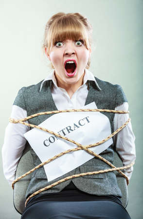 Afraid businesswoman bound by contract terms and conditions. Screaming scared woman tied to chair become slave. Business and law concept.