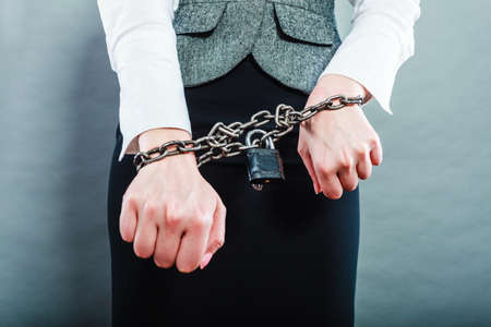 arrest women: Crime, arrest jail or business concept. Closeup woman with chained hands on grunge background
