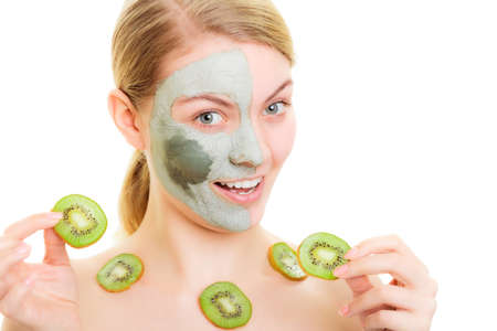 mud girl: Skin care. Woman in clay mud mask on face and necklace with slices of kiwi fruit isolated. Girl taking care of dry complexion. Stock Photo