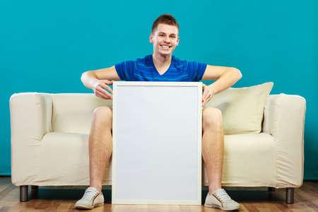 modelos hombres: Concepto de Publicidad. Joven sentado en el sof� con la tarjeta de presentaci�n en blanco. Modelo masculino que muestra la bandera de signo copia espacio cartelera para el texto en azul