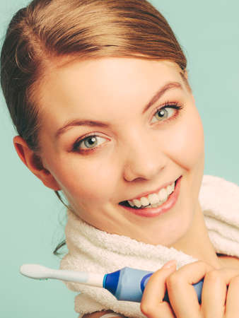 oral cavity: Pretty young girl with brush cleaning white using toothpaste. Happy woman cleaning her oral cavity caring about dental health holding toothbrush.
