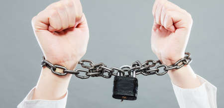 career woman: Crime, arrest jail or business concept. Closeup woman with chained hands on grunge background