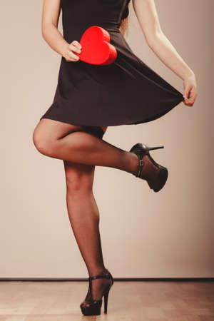 sexualidad: La belleza, la sexualidad y la seducción. Mujer atractiva con la parte del cuerpo rectángulo rojo del corazón presentes bailando regalo en el estudio. Foto de archivo