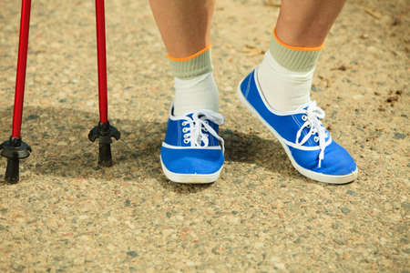 nordic walking: active mature lifestyle.  senior nordic walking in a countryside park Stock Photo