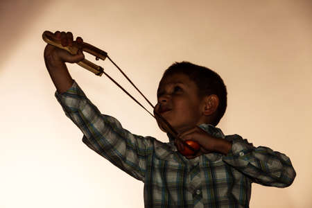 naughty boy: Children upbringing problems. Kid holding slingshot in hands. Bad naughty boy shoots from a wooden sling Stock Photo