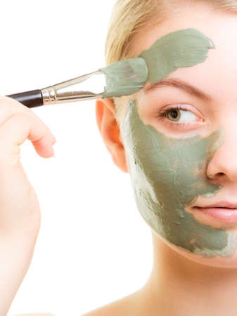 green and white: Skin care. Woman applying with brush clay mud mask on face isolated. Girl taking care of dry complexion. Beauty treatment.