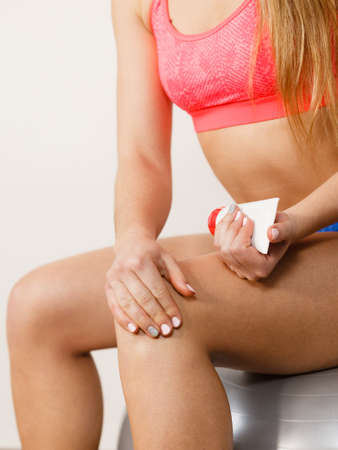 fit ball: Woman fitness girl sitting on fit ball putting ointment cream on bad injured knee. Sport training gym and health care