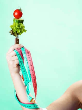 dietician: Diet and weight loss concept. Dietician woman hand with vegetarian food and colorful measuring tapes on green blue background. Stock Photo