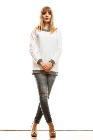 Fashion. Young blonde fashionable woman jeans pants white long-sleeved shirt. Female model posing isolated studio shot Stock Photo